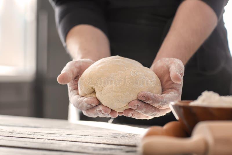 Panadero que sostiene la pasta sobre la tabla de cocina foto de archivo