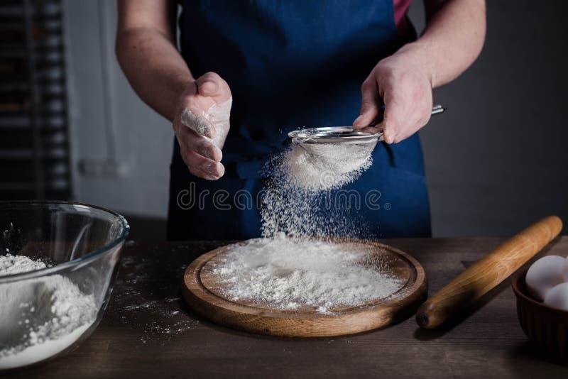 Panadero que tamiza la harina imagenes de archivo