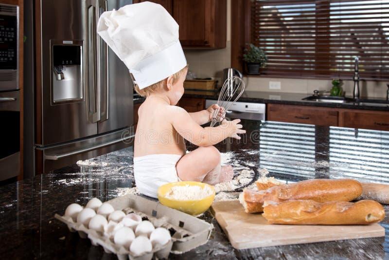 Panadero Sitting del bebé en cocina foto de archivo