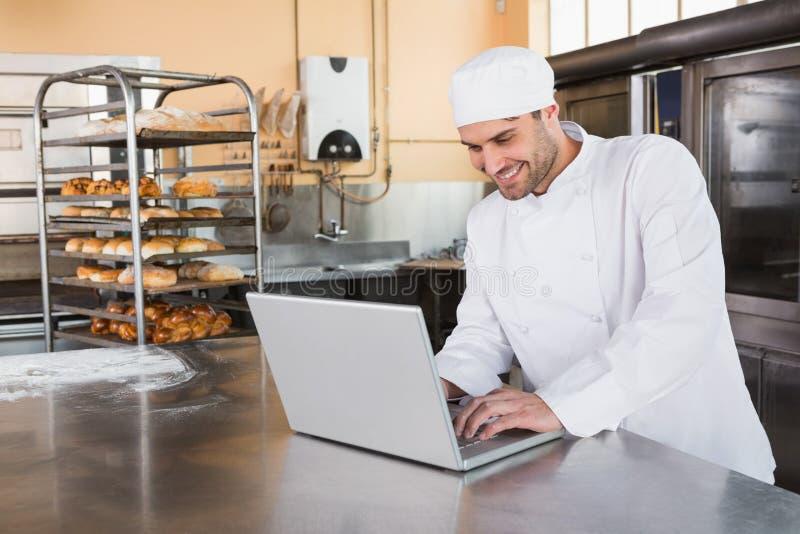 Panadero sonriente que usa el ordenador portátil en worktop fotos de archivo libres de regalías