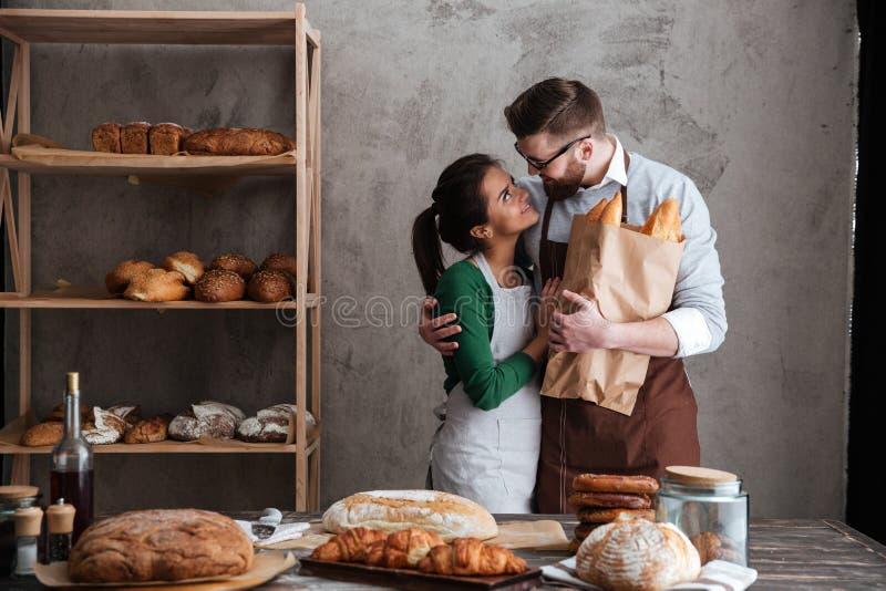 Panaderos cariñosos alegres de los pares que colocan el pan cercano fotografía de archivo libre de regalías