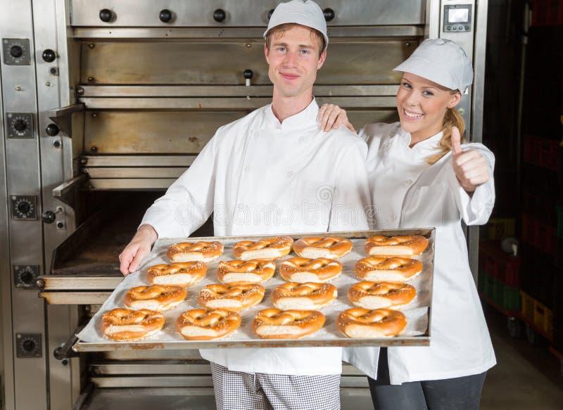 Panaderos con la bandeja de la hornada en la panadería que muestra los pulgares para arriba fotos de archivo