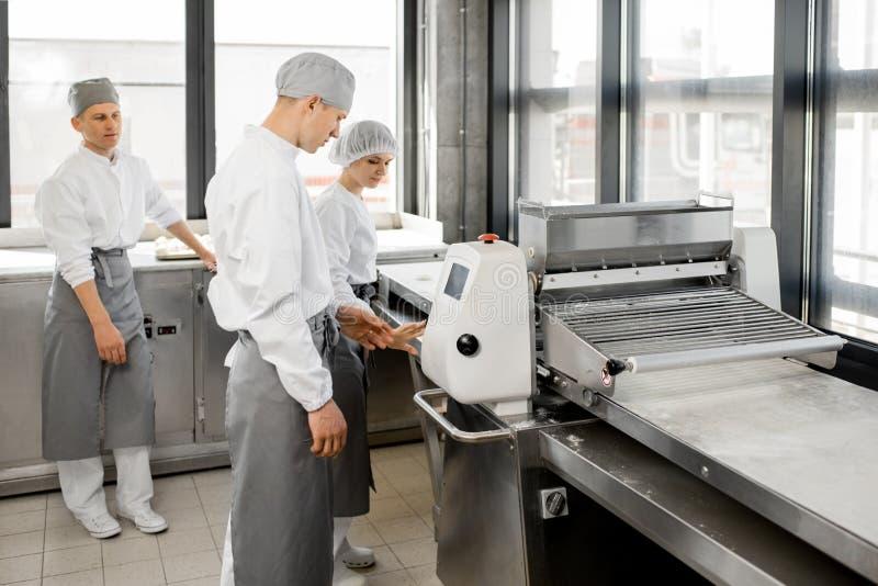 Panaderos que ruedan la pasta en la fabricación fotos de archivo