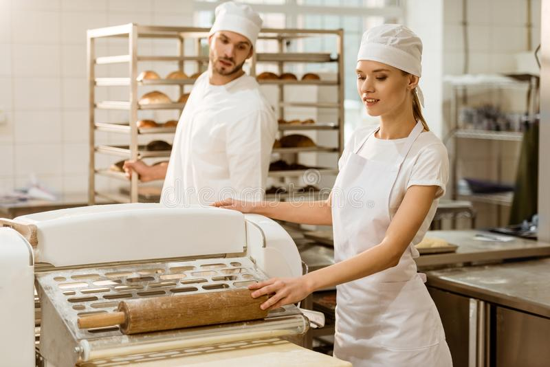panaderos que usan el rodillo industrial de la pasta imagenes de archivo