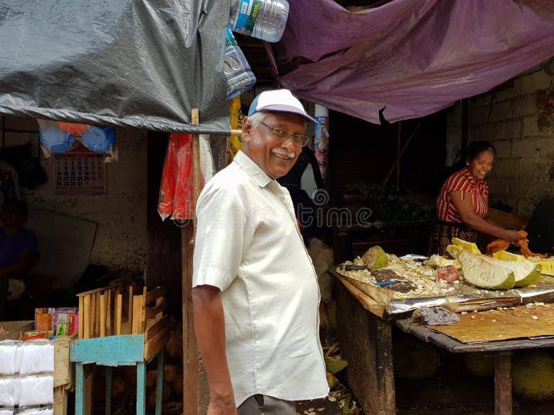 Panadura, Sri Lanka - 10. Mai 2018: Bemannen Sie das Lächeln an einem lokalen Markt von Obst und Gemüse von lizenzfreie stockfotografie