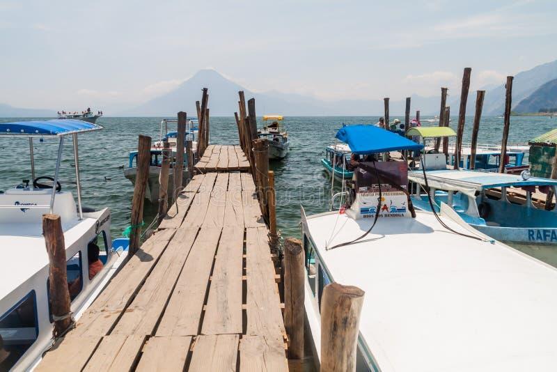 PANAJACHEL, GUATEMALA - 25. MÄRZ 2016: Hölzerner Pier in Panajachel-Dorf, Guatemala San- Pedrovulkan visibl stockfotografie