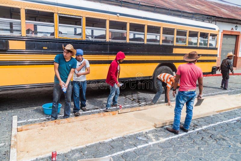 PANAJACHEL, GUATEMALA - 25 MARS 2016 : Les gens décorent des tapis de Pâques devant un bus local dans le village de Panajachel photographie stock