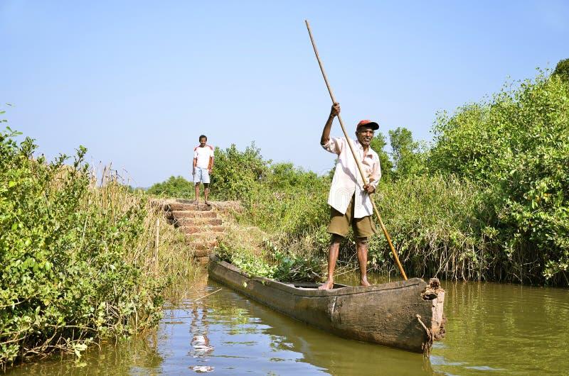 Panaji, Goa/India - 01/08/2012: Il pescatore indiano, un uomo anziano in una vecchia barca attacca fuori dalla riva fotografia stock