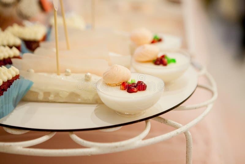 Panakota na ślubnym stole Delikatny biały ślubny tort i różni cukierki na stole zdjęcie royalty free