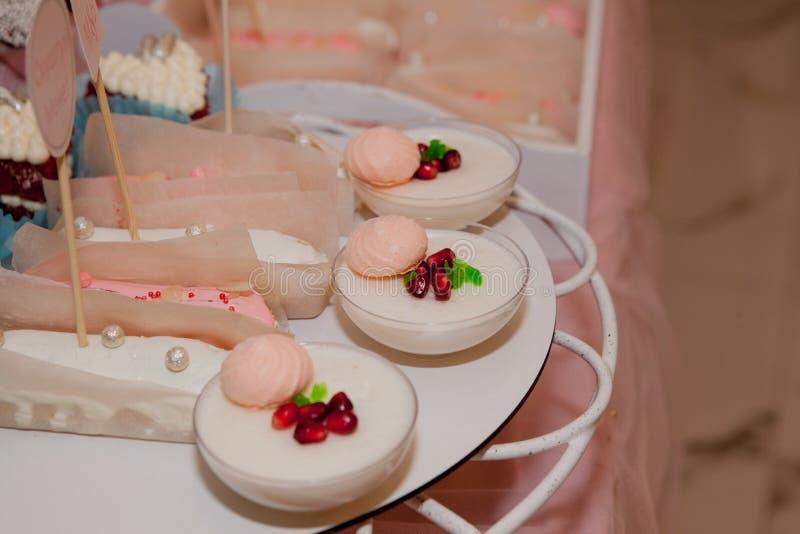 Panakota på den gifta sig tabellen Försiktig vit bröllopstårta och olika sötsaker på tabellen fotografering för bildbyråer
