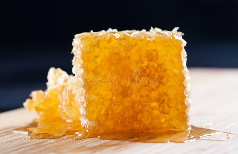 Panal natural en el tablero de madera, fondo oscuro textura con la miel fresca Profundidad baja del foco selectivo del campo fotos de archivo