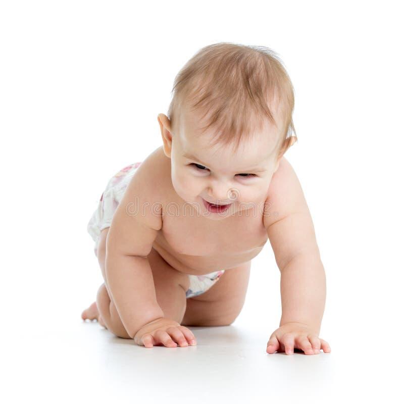 Panal weared bebé divertido que se arrastra en piso Aislado en el fondo blanco imagen de archivo