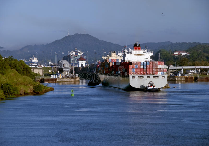 Panama Canal, Tugboat and Container Ship. A container ship gets a tug to the Miraflores Lock at the Panama Canal, a major transportation waterway connecting the stock photo