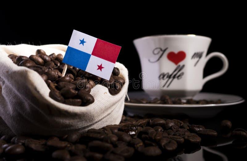 Panama-Flagge in einer Tasche mit Kaffeebohnen auf Schwarzem lizenzfreie stockbilder