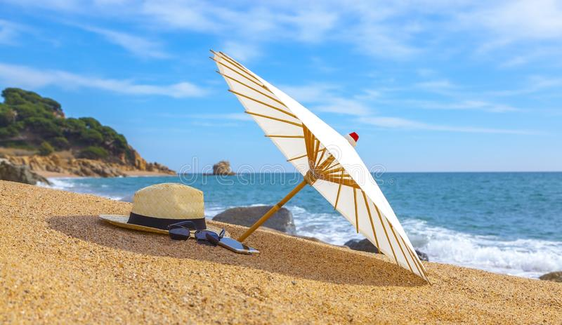 Panama hat and beach umbrella on the sandy beach near the sea. Summer holiday and vacation concept for tourism royalty free stock images