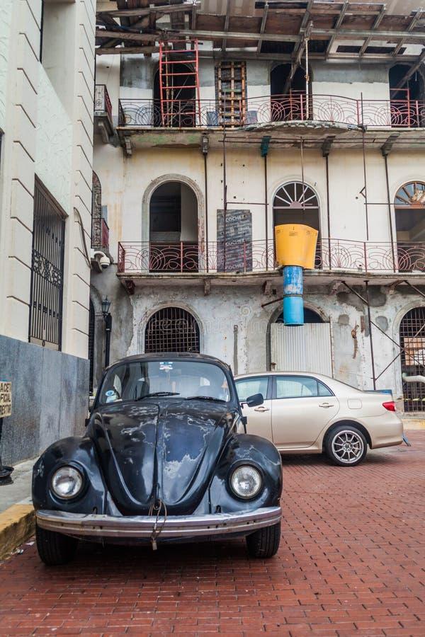 PANAMA-STADT, PANAMA - 27. MAI 2016: Zerfallenes Kolonialhaus und altes Volkswagen Beetle in historischer Mitte Casco Viejo von lizenzfreies stockbild