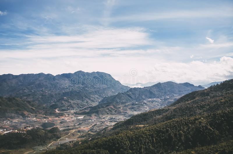 Panaromic och härlig sikt av hus och gröna terrassrisfält med blå himmel och moln på byn i Sapa royaltyfri foto