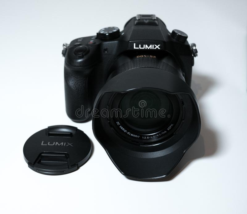 Panasonic Lumix FZ1000 Digital Camera on white desk. Front view. With lens cap removed stock photo