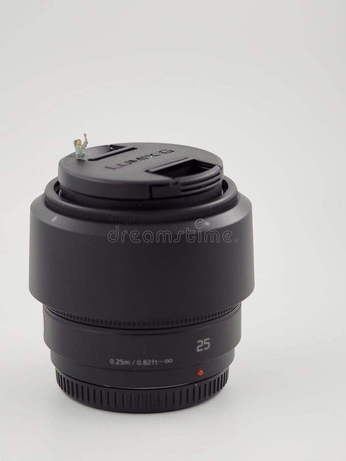 Miniature man on Lumix G lens. Panasonic Lumix G 25mm Camera Lens- Micro Four Third lens stock photo