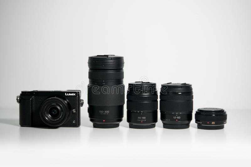 Panasonic Lumix GX80 Micro Four Thirds camera and several lenses on a white desk. Panasonic Lumix GX80 / GX85 Micro Four Thirds camera and several lenses on a royalty free stock images