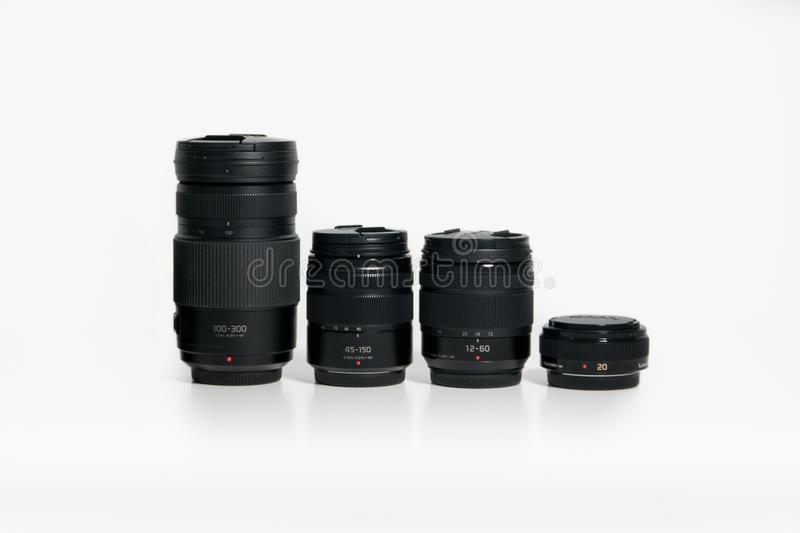 Panasonic Lumix Micro Four Thirds camera lenses on a white desk. Several different lenses, both prime and zoom royalty free stock image
