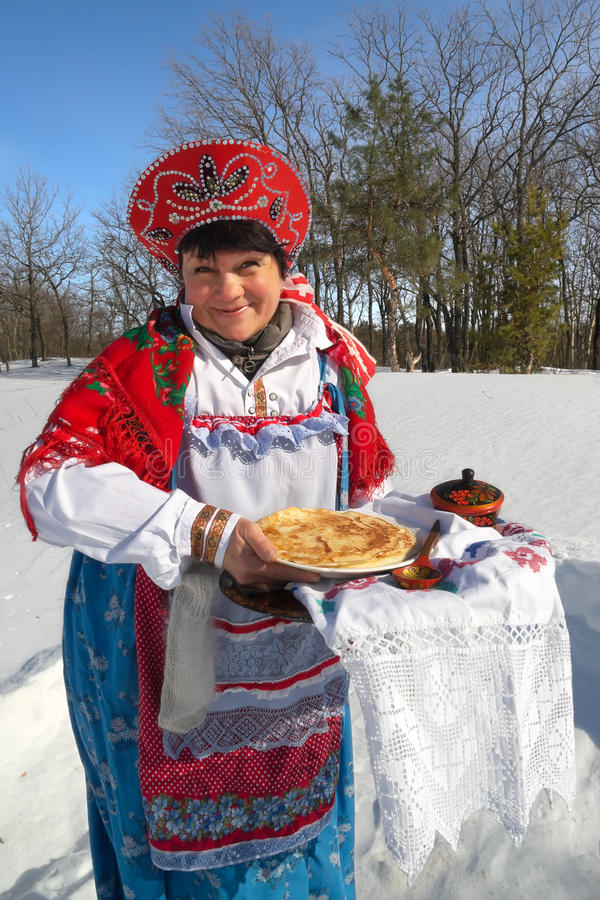 Pancake. Woman in folk clothing offers crepes stock images