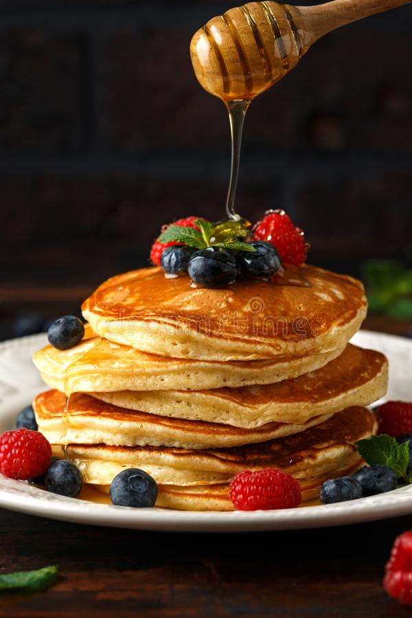 Pancake americani casalinghi con il mirtillo, i lamponi ed il miele freschi Stile rustico della prima colazione sana di mattina fotografia stock libera da diritti