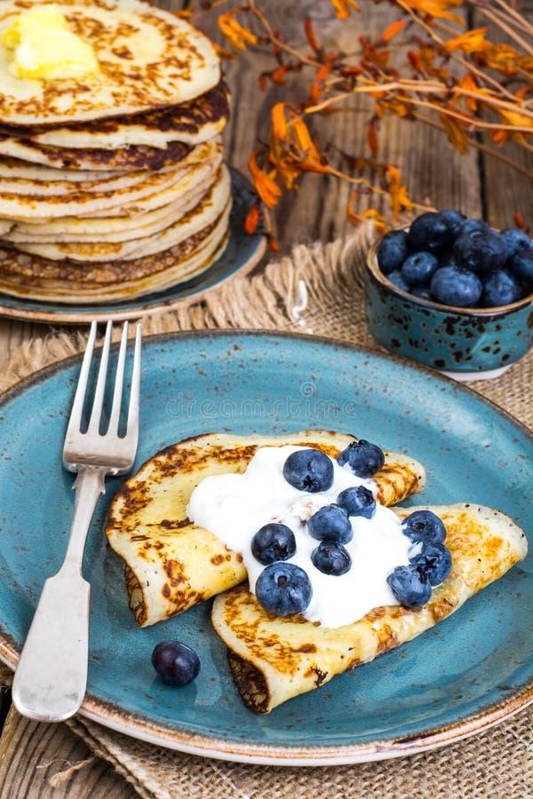 Pancake americani con salsa ed i mirtilli sul piano d'appoggio di legno immagini stock libere da diritti