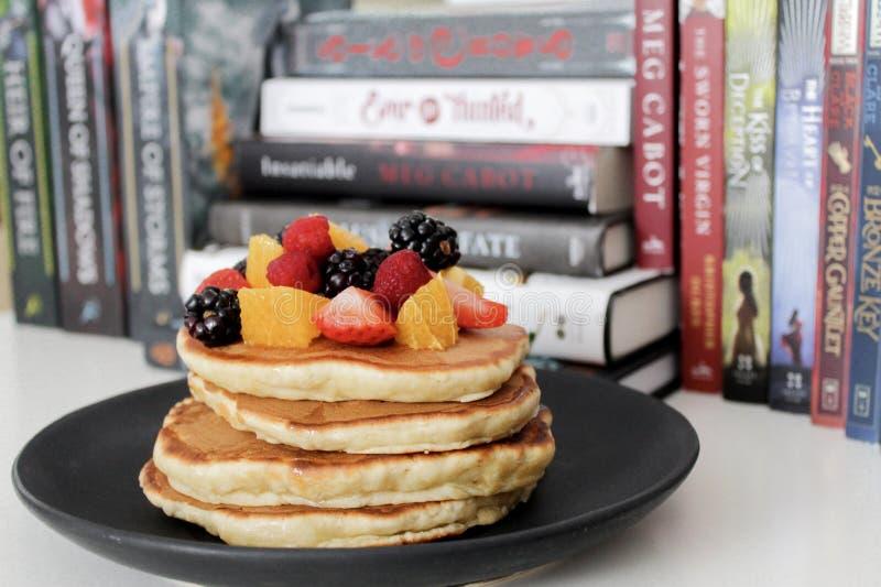 Pancake on Black Plate Near Books stock image