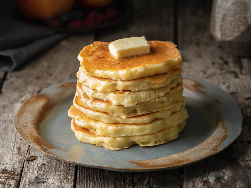 Pancake with butter, close-up. Dark moody old rustic wooden background.  royalty free stock photos