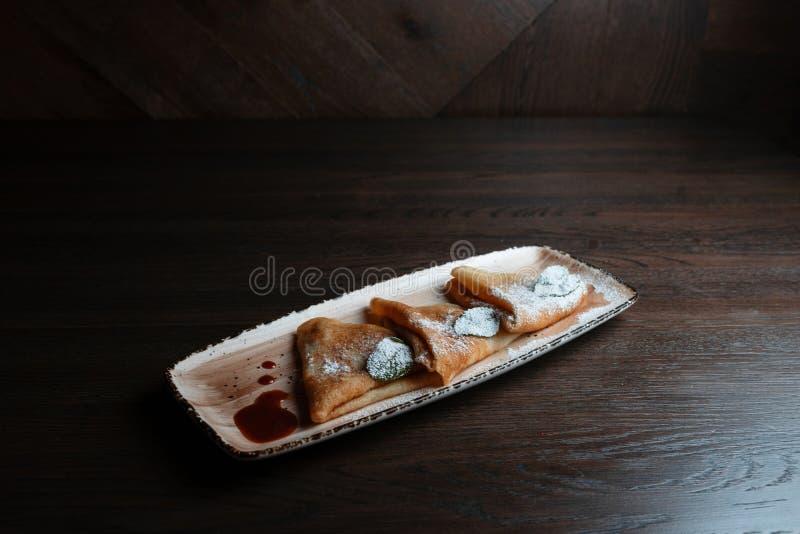 Pancake caldi dolci sottili con inceppamento dolce su un piatto in un ristorante Dessert squisito fotografie stock