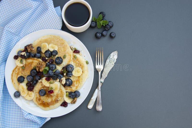 Pancake casalinghi con i mirtilli, la menta, i frutti ed il miele per la prima colazione - alimento sano casalingo Idea della pri immagine stock