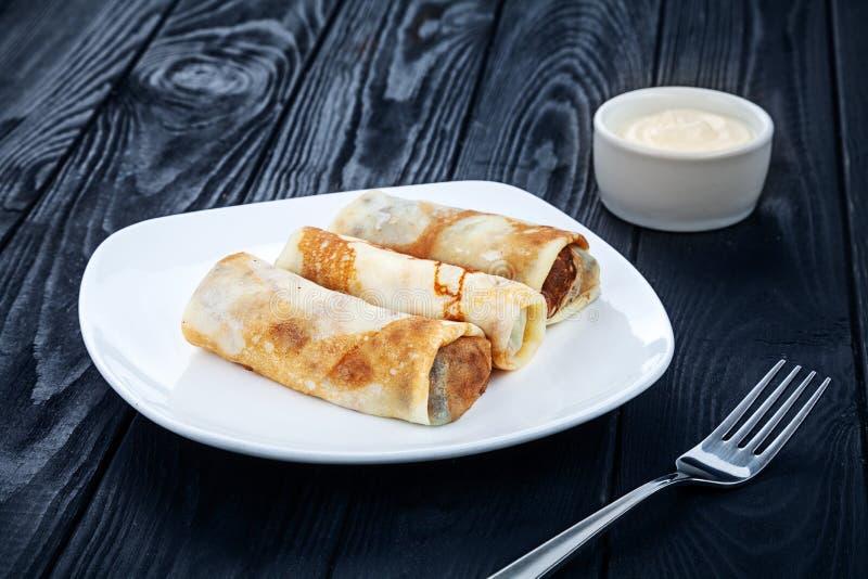 Pancake casalinghi con il riempimento su un fondo di legno scuro immagine stock libera da diritti