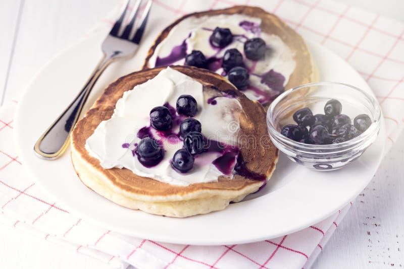Pancake casalinghi con la fine bianca del fondo del formaggio delle bacche miele e cremoso su tonificata immagini stock