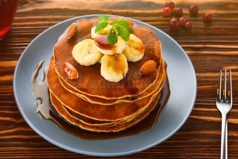 Pancake con caramello, la banana ed i dadi fotografia stock libera da diritti