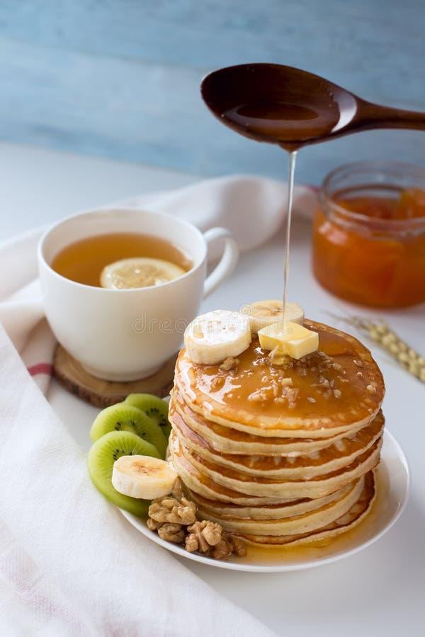 Pancake con i frutti, l'inceppamento ed il cappuccio di tè su una tavola bianca fotografia stock libera da diritti
