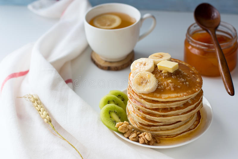 Pancake con i frutti, l'inceppamento ed il cappuccio di tè su una tavola bianca immagini stock libere da diritti
