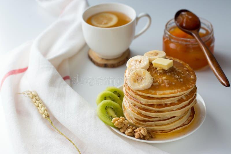 Pancake con i frutti, l'inceppamento ed il cappuccio di tè su una tavola bianca fotografie stock