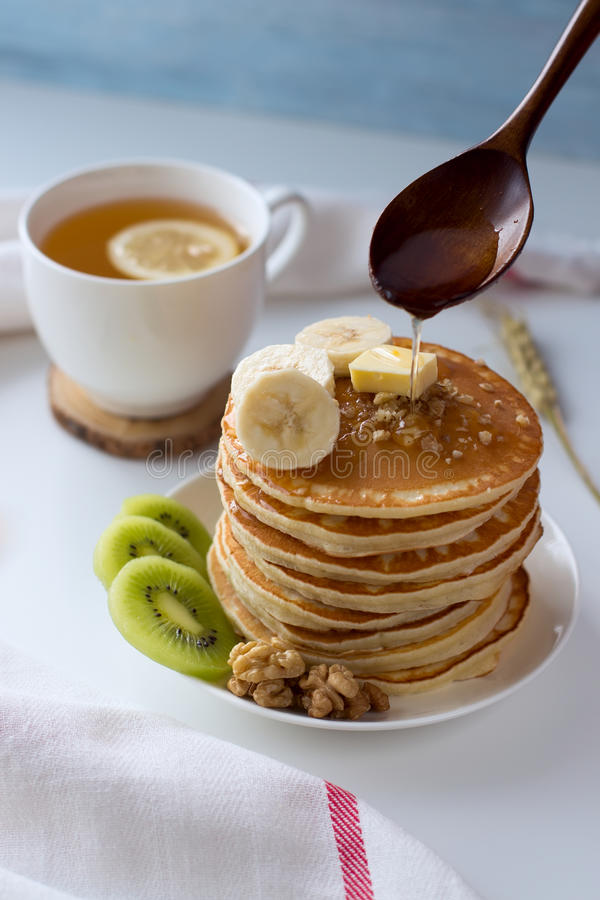 Pancake con i frutti, l'inceppamento ed il cappuccio di tè su una tavola bianca fotografia stock