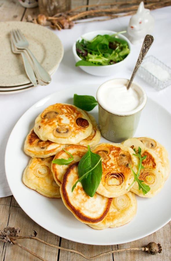 Pancake con i funghi e le cipolle, serviti con panna acida e un'insalata verde immagine stock