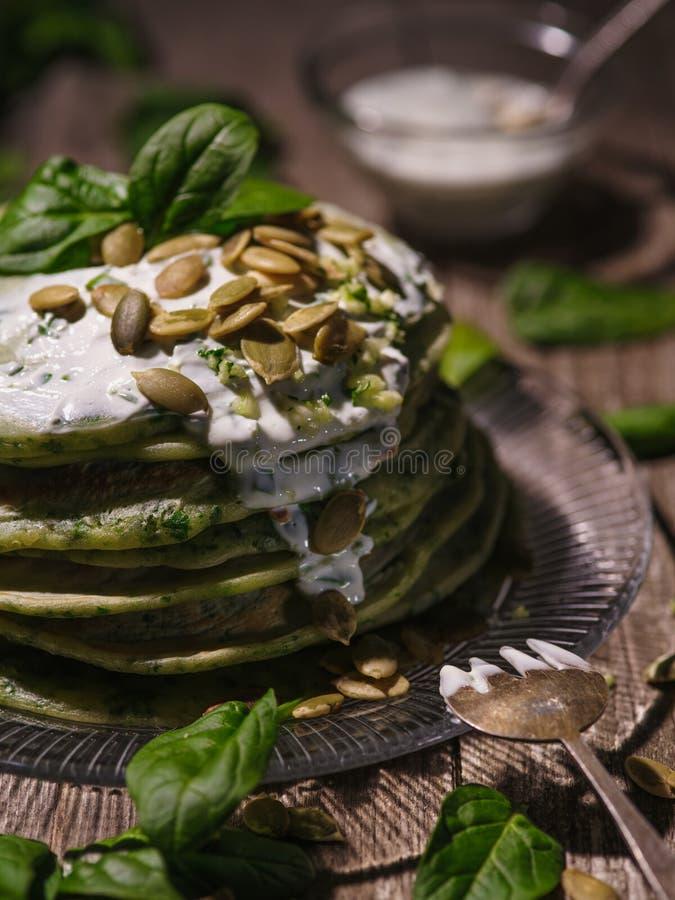 Pancake con i semi di zucca e degli spinaci su una tavola di legno conteggio fotografia stock libera da diritti