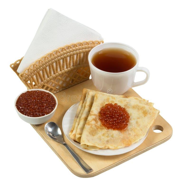 Pancake con il caviale su un bordo di legno isolato su bianco immagine stock