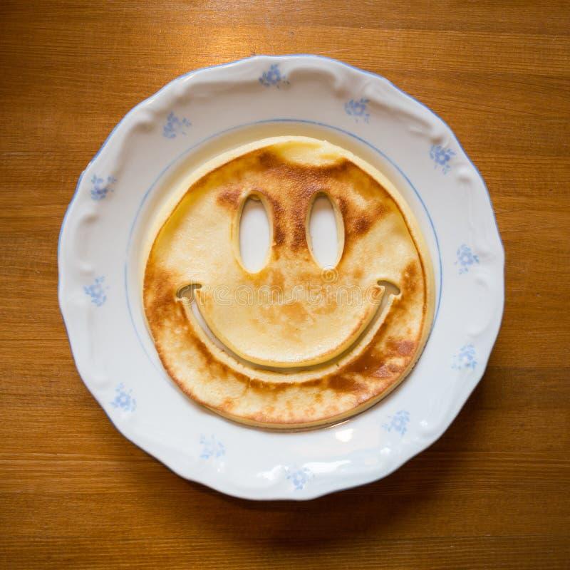 Pancake con il fronte sorridente sul piatto fotografia stock