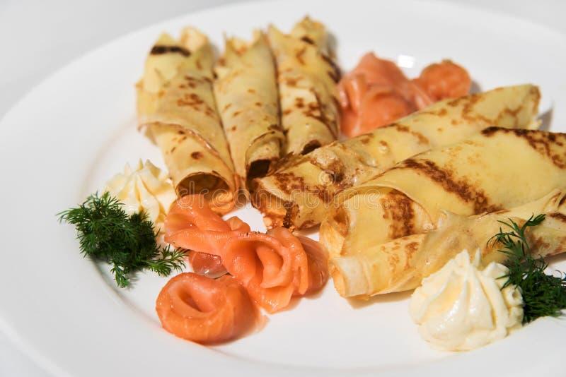 Pancake con il pesce e la besciamella rossi con aneto su un piatto bianco fotografia stock libera da diritti