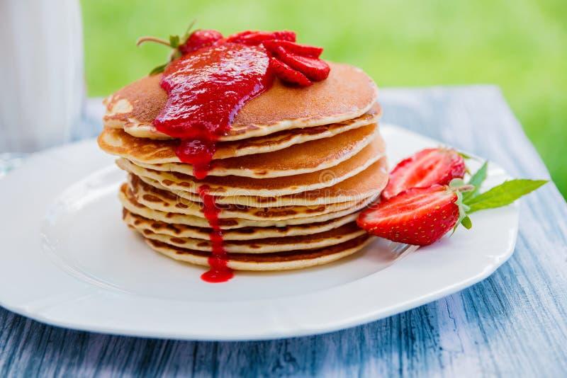 Pancake con la fragola e l'inceppamento freschi, vicino a latte di vetro sul fondo di legno del piatto bianco in giardino o natur immagini stock libere da diritti