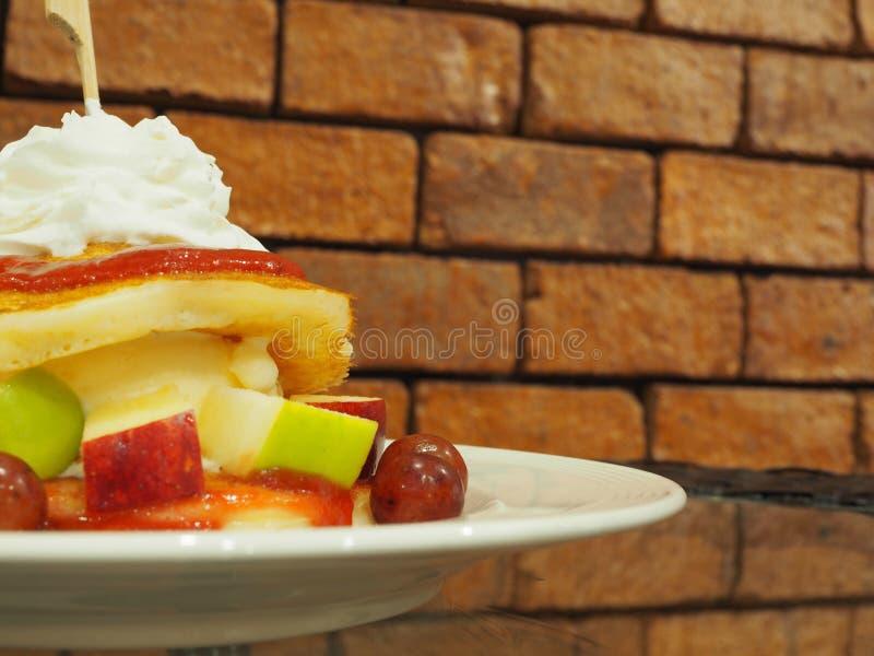 Pancake con la frutta fresca, panna montata sulla tavola di vetro con fotografie stock