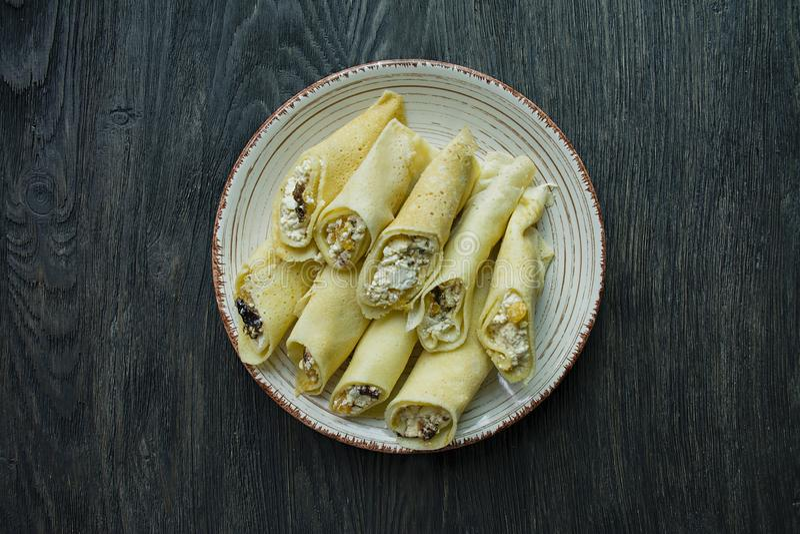 Pancake con la ricotta, le prugne, le albicocche secche e l'uva passa Vista da sopra Priorit? bassa di legno scura fotografia stock