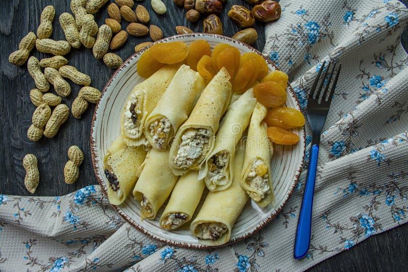 Pancake con la ricotta, le prugne, le albicocche secche e l'uva passa Vista da sopra Priorit? bassa di legno scura immagine stock