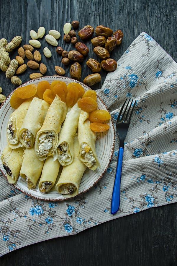 Pancake con la ricotta, le prugne, le albicocche secche e l'uva passa Vista laterale Priorit? bassa di legno scura fotografie stock libere da diritti