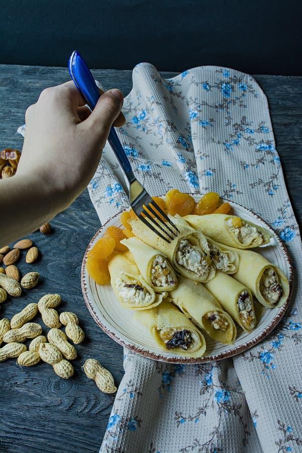 Pancake con la ricotta, le prugne, le albicocche secche e l'uva passa Vista laterale Priorit? bassa di legno scura fotografia stock